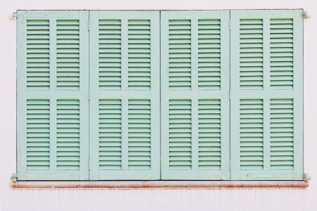 Detail of weathered green shutters of a spanish house Standard-Bild