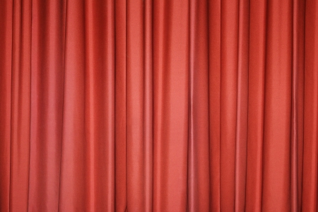 Detail of a red closed curtain in a theatre