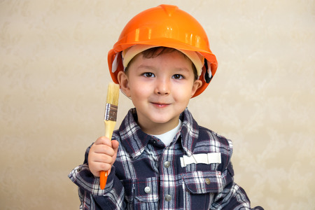 designer baby: Boy builder in a helmet and with a brush Stock Photo