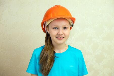 Girl the builder in a helmet and with a brush