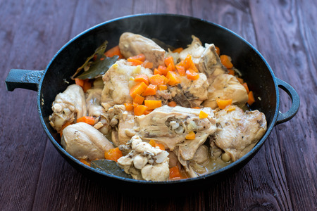 Braised chicken in a cast-iron frying pan on a wooden table