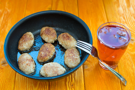 Fried meatballs in a pan on a wooden table Фото со стока