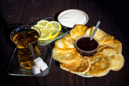 tea with pancakes and jam and sour cream on a wooden table Фото со стока