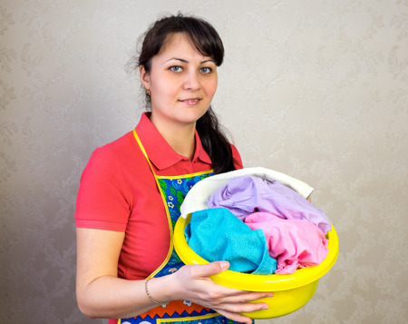 Girl with a basket of dirty linen color Фото со стока
