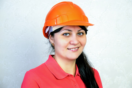 Girl the builder in a helmet. Close portrait of a smile Фото со стока