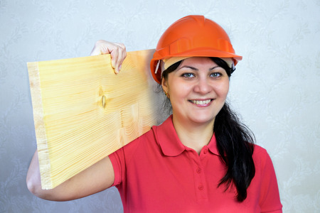 Girl the builder in a helmet with a plank of wood. Close portrait of a smile Фото со стока