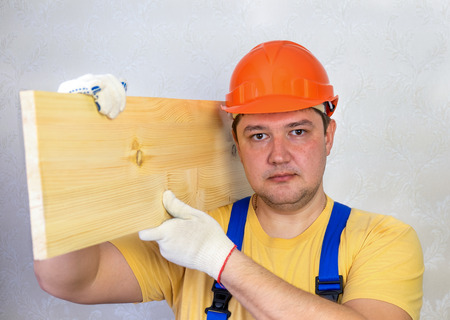 Male construction worker in a hard hat with a wooden board Фото со стока