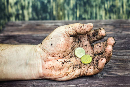 In the dirty hand of a coin Stock Photo