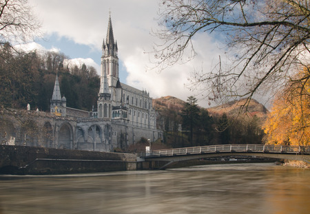 Sanctuaries of Lourdes seen from the Gave de Pau River. The bridge leading the major site of Roman Catholic pilgrimage and of miraculous healings, The Basilica of our Lady of the Rosary mooving water is at foreground