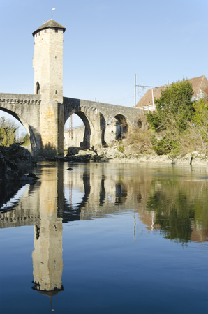 gascony: Old medieval fortified bridge across Gave de Pau River in Orthez reflecting in water