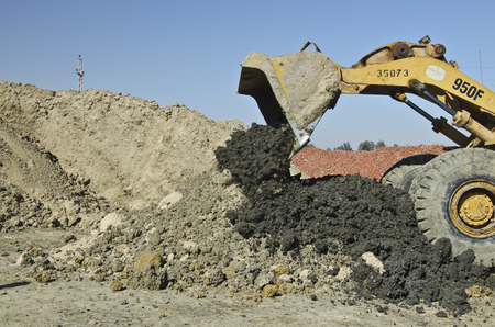 clays: Sand and different kinds of clays are mixing by tractor for brick manufacturing in the factory in Egypt, and clay brick wastes stock at background