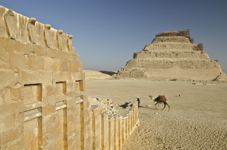 djoser: The first Egyptian Pharaoh Djoser Pyramid of 27 th century BC is Situated in the necropolis of Saqqara, ict stepped pyramid, Actually at restoration, Wall with Cobras of Heb-Sed festival Temple is at foreground Stock Photo