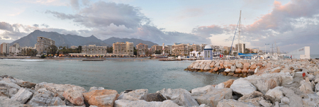 The Marbella city panorama seen from the harbor, coastal mountain range and cloudy sky at background are, sailing yacht club is right at Costa del Sol, Andalusia, Spain 写真素材