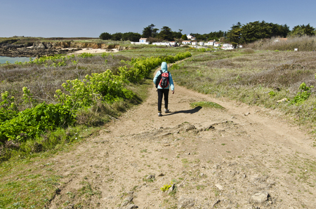 vendee: Girl teenager photographed from the back walk along the walk pass bordered with green vegetation. Rocky and sandy beach and lonely island houses are at background Stock Photo
