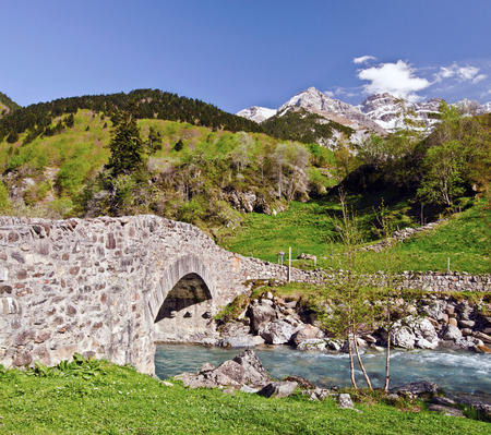gave: Nadau bridge through river Gave de Gavarnie is a stone bridge on the way from the village to the mountain Gavarnie Circus Ambama forest slopes and tops of snowy Pyrenees mountains at background Stock Photo
