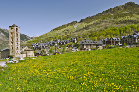 Tahull Village landscape with green meadow covered with yellow dandelion flowers is t foreground Famous Saint Climent de Taull church is at left and slopes of Pyrenees Mountains at background