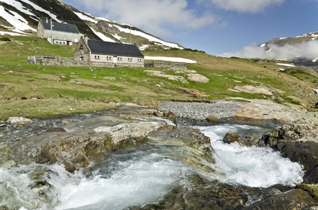 watercourse: Refuge and farmers house in Maillet high mountain tea in French Pyrenees in the way to Troumouse circus green spring grass and the watercourse at foreground Hautes Pyrenees France Pyrenees National Park.