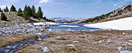 Panorama from top of MadriuPerafitaClaror Valley in spring the stream and the lake bordered with snow the mountain chain of Andorran Pyrenees and the sky at the background. UNESCO World Heritage Site