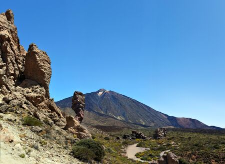 volcano slope: Mount Teide and Roque Cinchado seen from los Roques in Tenerife Island, the deap blue sky is in right background