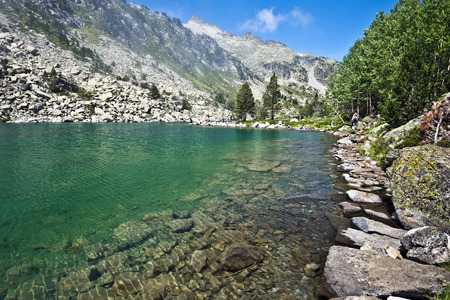 borderline: Picture of Laquette high mountain lake Neouvielle nature reserve of French Pyrenees, the rocky walking pass is following the water borderline, Ramougn peak hiding Neouvielle peak at background