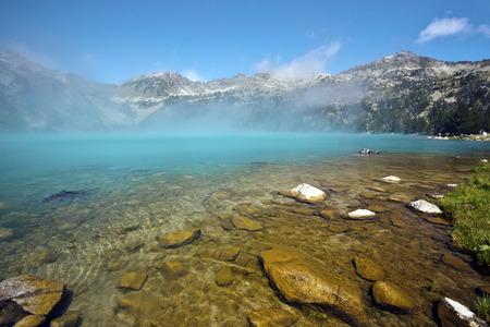 Colores Misterio del Lago Aubert en Neouvielle Reserva Natural, el agua transparente en primer plano, la niebla en el área del lago Da extraordinaria tono cian, cadena montañosa Horquette Aubert es en el fondo