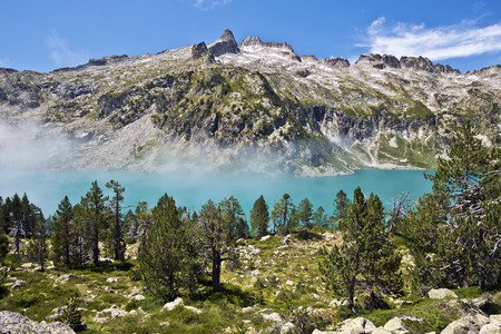 Neouvielle peak and Aubert Lake in French Pyrenees, seen from mountain pin forest Фото со стока