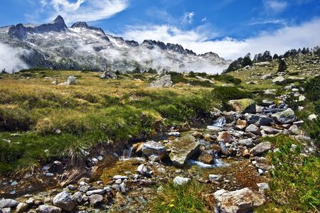 watercourse: Watercourse in Neouvielle mountain Massif in French Pyrenees, the Neouvielle; peak is at background Stock Photo