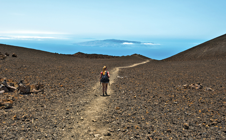 viejo: Young girl walks down Pico Viejo slope in Teide national Park, volcanic landscape, Atlantic Ocean and Gomera Island at the background, Tenerife, Spain