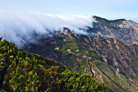 est: Spectacular szene of the mist coming through qui est mountains down to the valley of Anaga massif, the biosphere reserve in Tenerife Island. Stock Photo