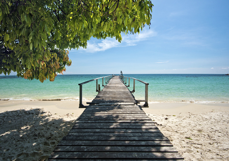 samet: Wooden jetty in tropical beach of Ko Samet island, the shadow from the coastline tree is at foreground, Thailand