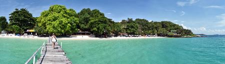 samet: Panorama of the tropical beach resort from Wooden jetty in Ko Samet island, young women walk to the beach, Thailand Stock Photo