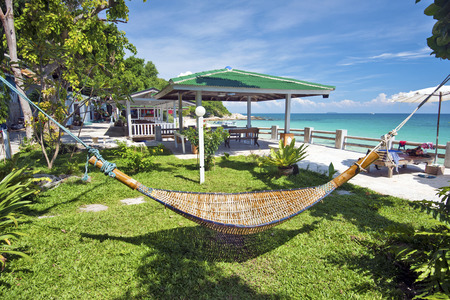 samet: Relaxation environment in tropical beach resort, the hammock is at foreground and the sea coastline is at background. Ko Samet island, Thailand.