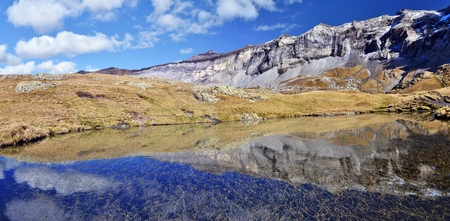 flank: Northern flank of Troumouse circus in French Pyrenees reflecting in lake water surface, with peaks, from right, Serre Mourene 3090 m, Troumouse 3085 m, Heid 3022 m, Blanc 2957 m and Gerbats peak 2904 m Midi Pyrenees, France