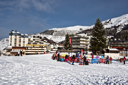 residences: Gourette, France- January 17, 2016. Place for kids in Gourette winter sports resort in Bearn Pyrenees. Aquitaine, Atlantic-Pyrenees. The Village residences are at background Editorial