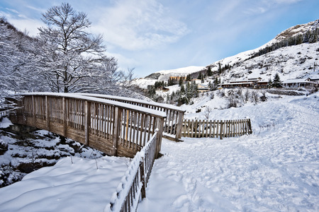 nature picture: Wooden Bridge across the river Valentin In Gourette town in winter time in snowy soft early morning light. This peaceful nature picture of is nearby popular winter sports resort in Bearn Pyrenees, Aquitaine, France.