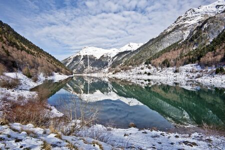 pyrenean: Winter picture of Pyrenean Fabreges Lake in Ossau Valley. The Sagette mounting is at background, Mountain landscape reflecting in water mirror. Bearn, Atlantic-Pyrenees, Aquitaine, France Stock Photo