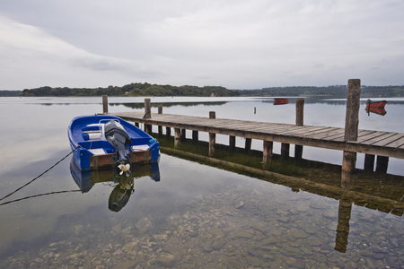 Blue motorboat and wooden jetty is in the border of Laguna Urbino in Corsica Island. Stock Photo