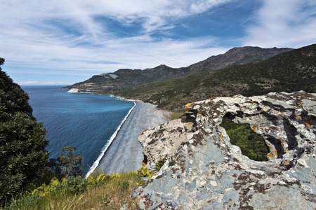corse: Nonza beach seen from tower hill making a part of Western coastline of Cap Corse Peninsula, asbestos stone pit Canari is at background, Haute-Corse, France