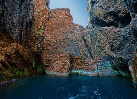 Arrow corridor and grotto in Scandola Nature reserve, vertical basaltic walls are around, Corsica Island, Corse-du-Sud, France Stock Photo