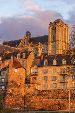 gallo: Gallo-Roman walls, buildings of old city and Le Mans Cathedral Saint Julian in evening lights seen from river Sarthe, Pays de la Loire.
