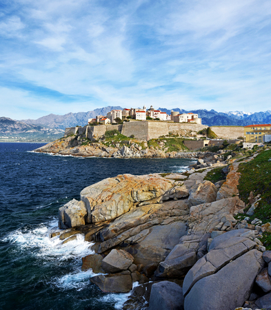 Calvi Citadel and Old city seen from Revellata Peninsula, Coast Rocks are at foreground, Balagne, Haute-Corse, France