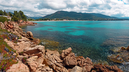 Panoralma of Sagone seaside resort in Corsica, washed with waters of Mediterranean Sea, Mountains and cloudy sky are at background. Corse-du-Sud, France Фото со стока