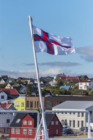 National Flag of Faroe Islands with the background of Torshavn city and blue sky out of focus
