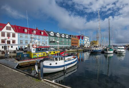 Torshavn, Faroe - July 11, 2018 Vestaravag harbor in Torshavn with its boats, yachts and colorful quayside gabled buildings, Faroese island of Streymoy