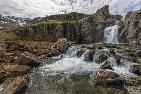 River, Waterfall and mountain landscape in Fjardabyggd municipality in Eastern Iceland, in the way to Mjoifjordur