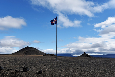 The landscape of Odadahraun desert in Central Highlands of Iceland and Icelandic national flag in top of the high pole Stock Photo