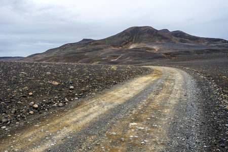Austurleid road coming through desert  hills covered with volcanic sender and rocks in Fljotsdalsherad municipality in Iceland