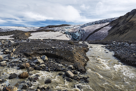Water races coming from the Glacier of massive Kverkfjoll in Icelandic National Park Vatnajokull, ice front and the grotto are background