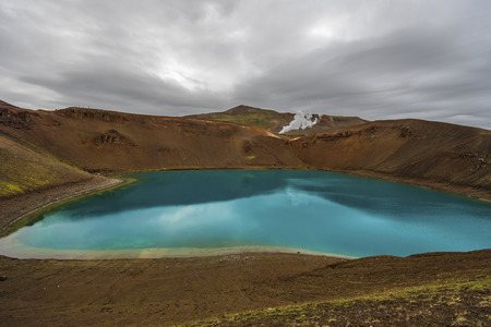 Ver en el cráter volcánico Krafla y el lago Viti en el norte de Islandia, el vapor de la unidad de la planta de energía geotérmica está en el fondo, la región de Nordurland eystra. Foto de archivo