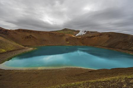 Vista sul cratere vulcanico Krafla e sul lago Viti nel nord dell'Islanda, il vapore dell'unità della centrale geotermica è sullo sfondo, regione di Nordurland eystra. Archivio Fotografico